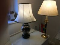 Two table lamps, one with black floral base and the other brass coloured