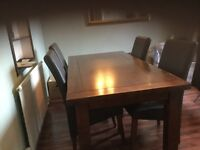 Mahogany dining room table and 4 brown leather chairs