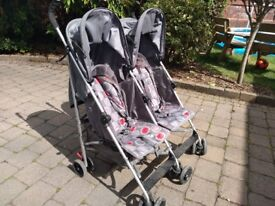 Mothercare double stroller with footmuffs and raincover