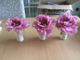 3 pink artificial flowers in cream vases