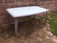 Glass top garden table with central hole for parasol / sun shade