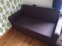 A two seater dark grey Ikea sofa bed.