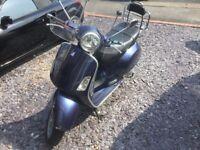 Vespa piaggio 200cc scooter in metallic blue with rear chrome rack and Vespa visor