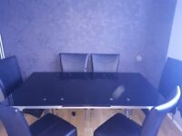 Extending black glass table and 6 faux leather chairs