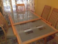 Nearly new extenable dinning table with glass top and four matching chairs