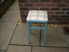 A four legged wooden stool with square seat and painted light blue.