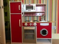 A Great LittleTrading Company kids role play kitchen with oven, washing machine and fridge freezer.