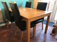 Wooden beech/pine dining table and four highback faux leather chairs
