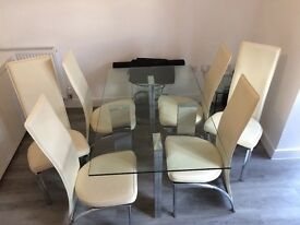 Glass dining table with cream faux leather chairs