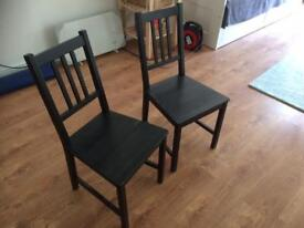 2 black Ikea wooden chairs