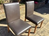 Two brown faux leather dining chairs