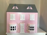 Pink wooden dolls house with furniture and family