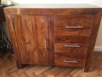 Wooden storage cabinet with three drawers.