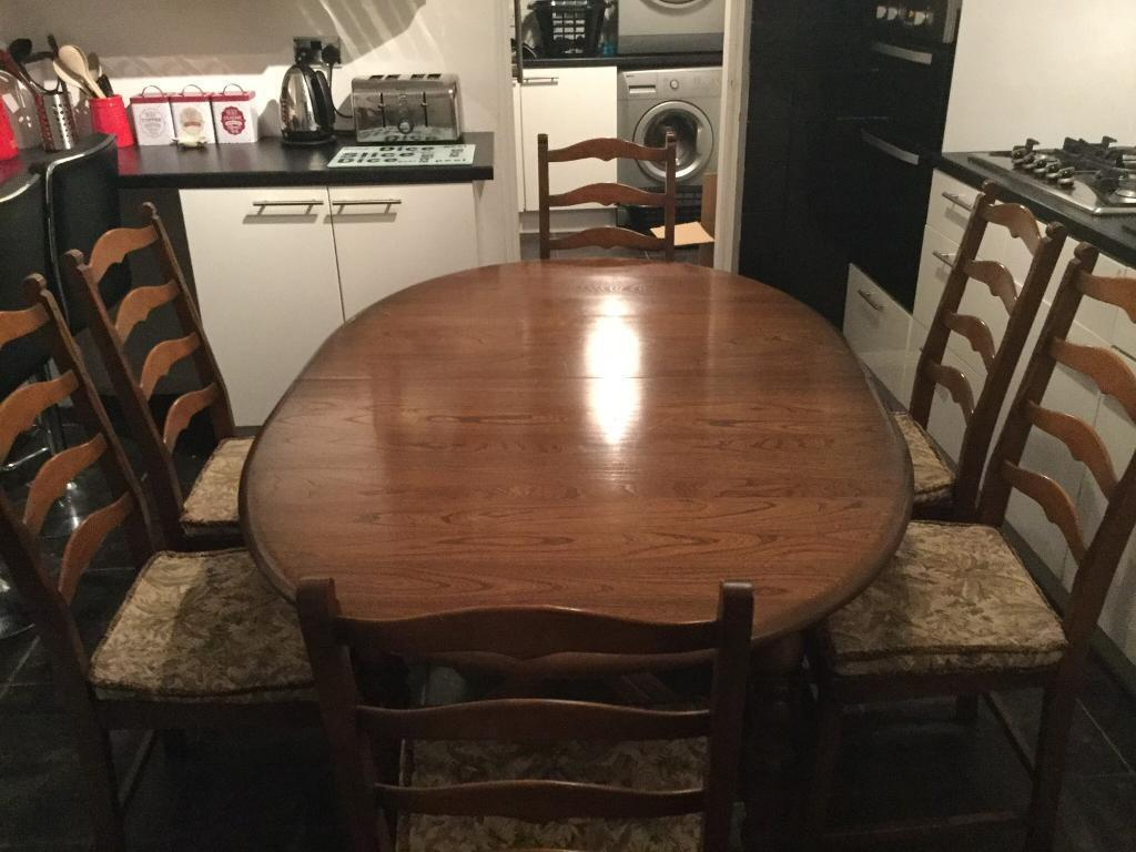 Ercol dining table and 6 ladder back chairs.