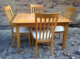 Light wooden table & 4 cream chairs some wear on 2 chairs, could easily be recovered though
