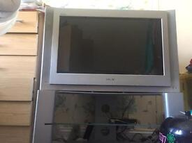 Silver Sony tv with stand