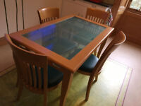 Glass-topped dining table with 4 comfortable chairs