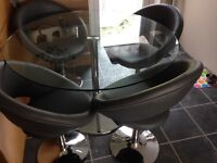Round glass table with 4 grey swivel chairs from Dwell