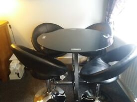 dining table and 4 chairs. Black glass and polished chrome table faux leather chrome swivel chairs.