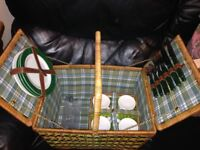 Wicker picnic basket with accessories such as plates and cups