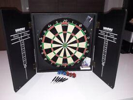 Winmau dartboard in white cabinet