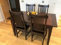 Extendable dining table with four chairs, solid wood. Sits 4 to 6 people