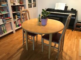 Round wooden dining table and two chairs