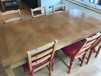 Large wooden dining table and 6 wooden chairs with red covers