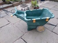 Plastic wheekbarrow in good working condition despite looking a little tired.