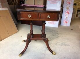A mahogany pedestal side table with brass claw feet