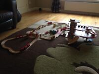 Plan wooden car garage and 50 piece wooden train set with trains, carriages, cars and accessories.
