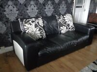 LEATHER SOFA COUCH BLACK WITH WHITE ENDS AND WHITE PIPING /ALSO FOOT STOOL/ AND CUSHINGS