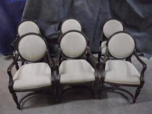 6 wood chairs, highly carved frames with arms. White patterned fabric back pad and seat