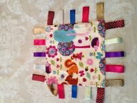 Taggies made with cotton fabric with various coloured ribbons round the edge. 20cm x 20cm