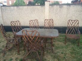 Garden Table & Chairs. Glass top table on cane structure with 6 chairs.