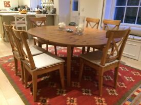 Solid pine extending dining table and 6 chairs, seats 4-8.