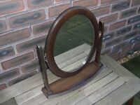 A wood surround oval dressing mirror.