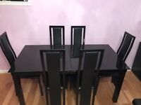 Harvey's black glass dining table with 6 chairs