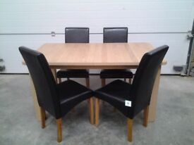 New Extendable dining table and 4 black faux leather chairs. Boxed Can deliver.