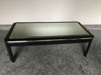 Black lacquer finish mirror top dining table with gold trim.