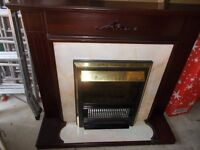 electric fire in attractive dark wood surround with carved features at top with mantlepiece