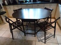 Brown butterfly dining table with 4 wooden folding chairs, space saving