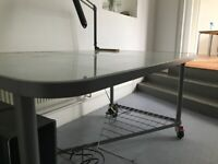 Glass topped table with steel frame and legs on casters