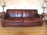 A matching pair of brown, leather 3 seat sofas.