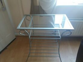 Tall glass table with two metal shelves.