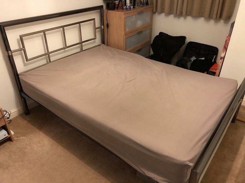 Metal framed double bed and mattress.