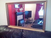 Bevelled glass mirror in gold look frame In good condition