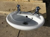 sink and taps. Wall mounted small cloakroom basin.