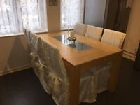 Solid pine dining table with frosted glass centre piece and 6 chairs with covers