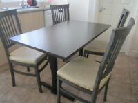 Solid oak chairs, leather seats and dining table with heavy cast iron base